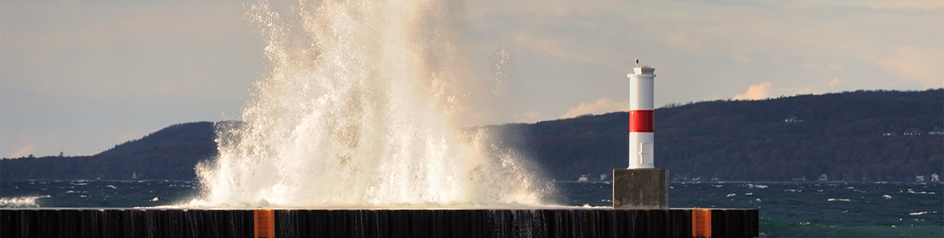 Water crashing over a dock with hillside in the background.